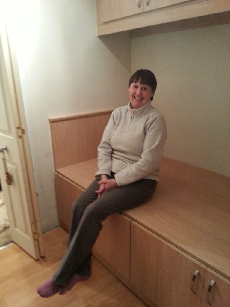 Mrs H sat On cabin Bed
