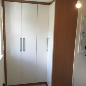 L-shaped wardrobe with fitted doors and handles